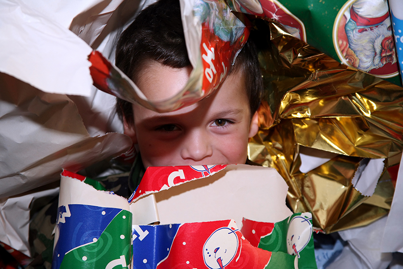 Child hiding in wrapping paper