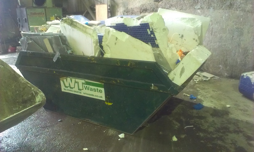 A skip overflowing with general waste.
